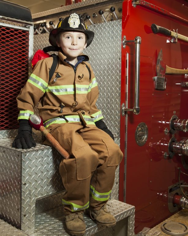 Young boy dressed as a fire fighter and sitting on a fire truck.